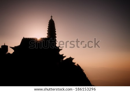 Ji Zu Shan Temple (Chicken's Foot Mountain Temple) Silhouetted against the Early Morning Sunrise. An active Buddhist temple in Yunnan province, China. - stock photo