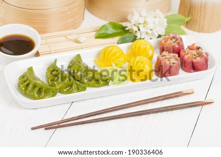 Jiaozi, Har Gow, and Siu Mai - Chinese colourful steamed dumplings. Traditional dim sum set. - stock photo