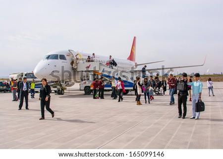 JIAYUGUAN,CHINA-OCTOBER 13:Chinese people just arrive and having left the aircraft at Jiiayuguan airport on October 13,2013 in Jiuguan,Gansu,China. - stock photo