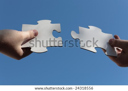 Jig Saw Puzzle Pieces Fitted with Bare Hands - stock photo