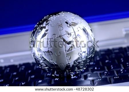 Jigsaw globe puzzle on laptop - stock photo