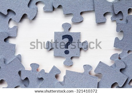 Jigsaw puzzle and question mark on wooden background - stock photo