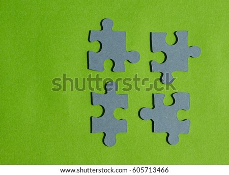 Jigsaw puzzle pieces on bright green background, horizontal view with copy space