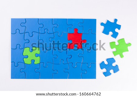 Jigsaw puzzle with different colored pieces signifying concepts of diversity, equality, community and being the odd one out - stock photo