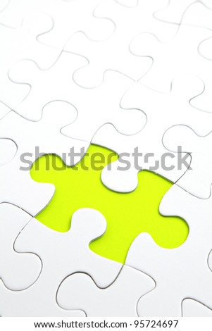 Jigsaw puzzle with green piece missed - stock photo