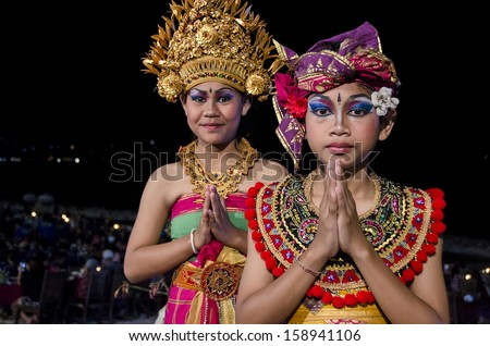 JIMBARAN, BALI, INDONESIA - OCTOBER 13: Two unidentified teenage girls entertain tourists with traditional dancing on the  beach on October 13, 2013 in Jimbaran, Bali, Indonesia.  - stock photo