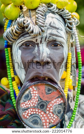 JINKA, ETHIOPIA, - 10 AUGUST: unidentified woman from Mursi tribe with big lip plate, in  Jinka Ethiopia, on 10 August 2014. The bigger the lip plate, the more beautiful the woman is considered.  - stock photo