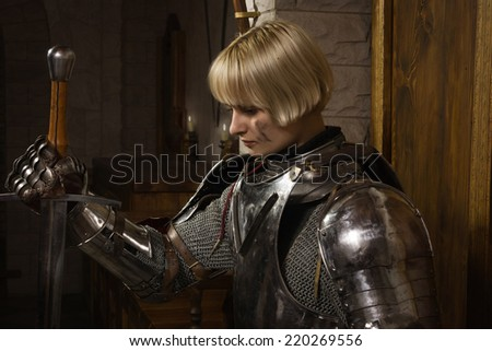 Joan of Arc. Girl in a knight's armor in the interior of a medieval castle - stock photo