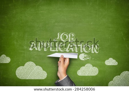 Job application concept on green blackboard with businessman hand holding paper plane - stock photo