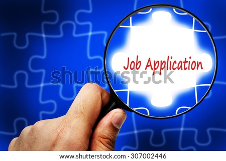Job Application word. Magnifier and puzzles. - stock photo