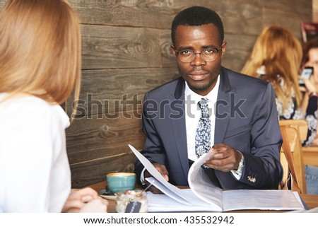 Job interview and employment concept. Portrait of confident African businessman in glasses looking at the camera with serious expression, holding job application while interviewing redhead woman - stock photo