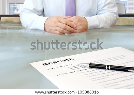 Job Interview. Job interview in the office with focus on resume and pen - stock photo