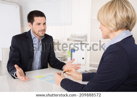 Job interview or meeting situation: business man and woman at desk. - stock photo