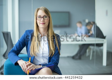 Job interview. Smiling businesswoman with notepad and pen in office. - stock photo