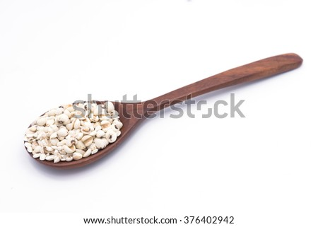 job's tears on wooden spoon , chinese pearl barley , on white background