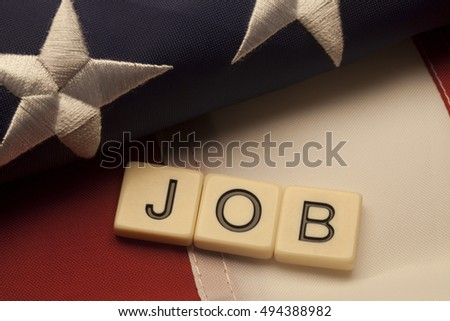 Job scrabble letters on American flag background. Concept of political issue.