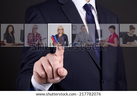 job search concept - businessman pressing an imaginary buttons with people portraits over dark background - stock photo