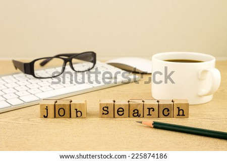 Job search word on rubber stamps place on table with a cup of coffee, keyboard and glassess, concept for employment - stock photo