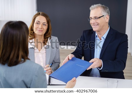 Job seeker handing over her CV to a smiling business manager sitting with his female colleague to conduct the interview