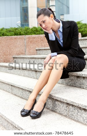 jobless businesswoman,  depressed and worried woman sitting on stairs office building - stock photo