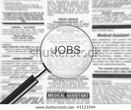 Jobs ad through a magnifying glass - stock photo