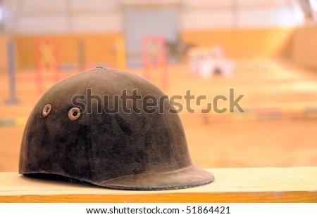 Jockey helmet over riding school background - stock photo