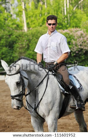 Jockey in glasses seat on horse on hippodrome