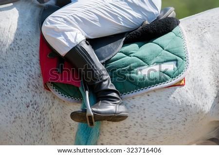 Jockey leg closeup sitting on racing horse - stock photo