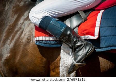 jockey leg sitting up in a saddle detail on thoroughbred racing horse - stock photo