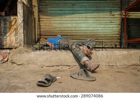 JODHPUR, INDIA - 10 FEBRUARY 2015: Drunk Indian man passed out on street. - stock photo