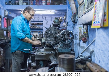 JODHPUR, INDIA - 17 FEBRUARY 2015: Mechanic working late in workshop with scattered equipment and machinery. - stock photo