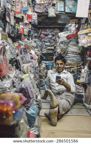 JODHPUR, INDIA - 07 FEBRUARY 2015: Store owner sits on floor of little textile shop overflown with different merchandise and waits for customers. Post-processed with added grain and texture. - stock photo