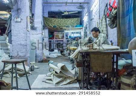 JODHPUR, INDIA - 10 FEBRUARY 2015: Tailor at work in textile factory after working hours. - stock photo