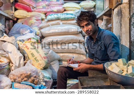 JODHPUR, INDIA - 10 FEBRUARY 2015: Young India man sits in store and writes down days income in notebook. Late working hours are common in India's markets. - stock photo
