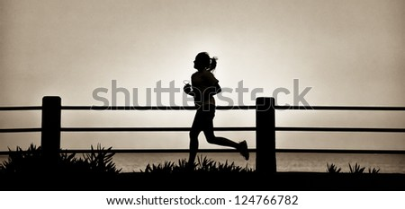 Jog along the ocean front in early morning light - stock photo