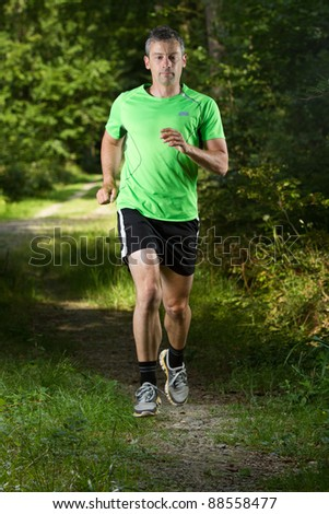 jogger on a trail in the forest - stock photo
