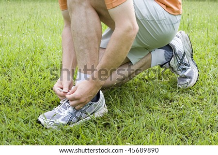 Jogger or runner tying his shoes in green grass - stock photo