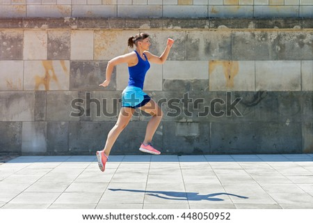 Jogger woman jump by the wall in city. - stock photo