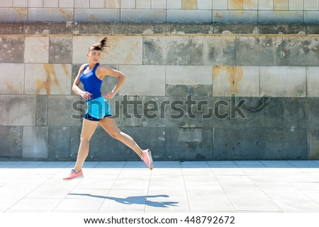 Jogger woman jump by the wall in city. look behind.