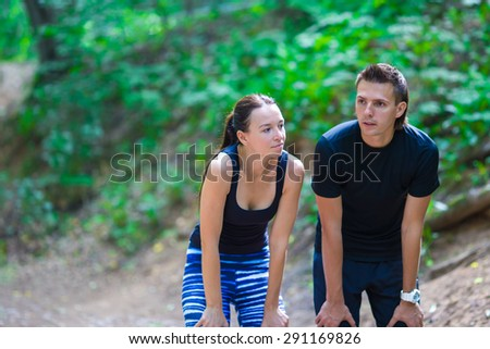 Jogging active couple taking break during training outdoors in park - stock photo