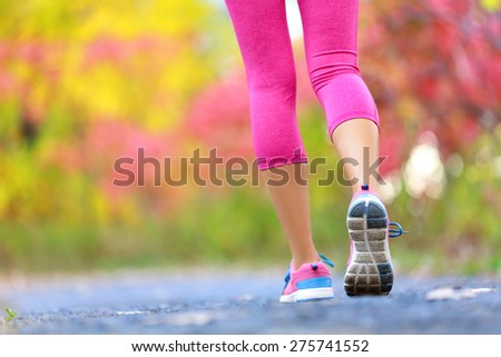 Jogging and running woman with athletic legs on jog or run on trail in forest in healthy lifestyle concept with close up on running shoes. Female athlete jogging and training outdoors in autumn fall. - stock photo
