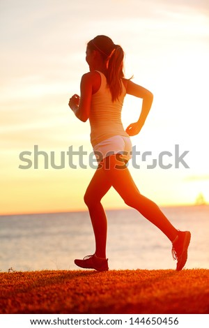 Jogging athlete woman running at sun sunset beach. Fitness runner girl training outside by the ocean sea in beautiful sunset or sunrise in full body length in summer. - stock photo