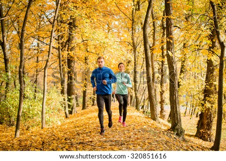 Jogging couple - young man and woman competing, man first - stock photo