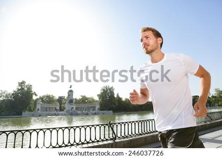 Jogging man running in city park El Retiro Madrid. Male runner exercising and training on run living healthy active lifestyle in Buen Retiro Park, Parque el Retiro in Madrid, Spain, Europe. - stock photo