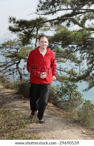 Jogging on footpath against sea - stock photo