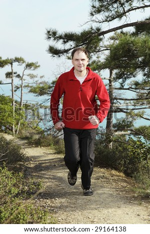 Jogging on footpath under pine trees against sea - stock photo