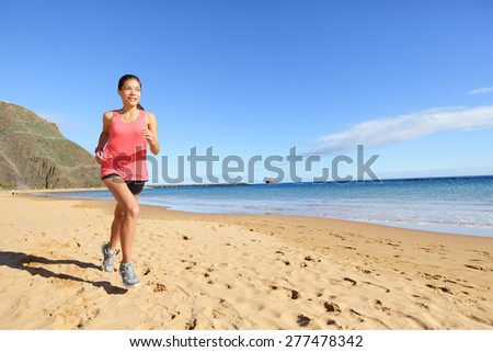 Jogging sports athlete runner woman running on beach sweating. Fit exercising female fitness model working out training for marathon run. Biracial Asian Caucasian sports girl. - stock photo