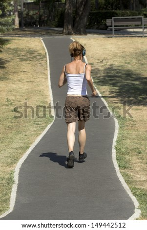 Jogging woman running in city park - stock photo