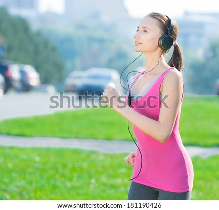 Jogging woman running in city park in sunshine on beautiful summer day and listening a music in headphones. Sport fitness model caucasian ethnicity training outdoor for marathon. - stock photo