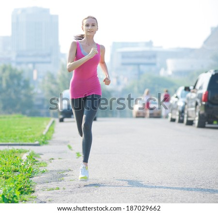 Jogging woman running in city park in sunshine on beautiful summer day. Sport fitness model caucasian ethnicity training outdoor for marathon.